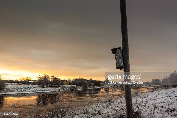 old birdhouse on pole by river against sky during winter - heinovirta stock pictures, royalty-free photos & images