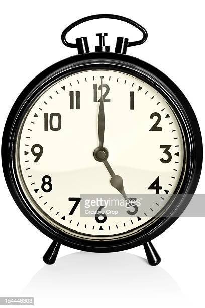 Old, black alarm clock showing 5 O'clock 5am / 5pm