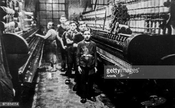 Old black and white archival photograph showing female worker and child labourers posing in spinning mill in the early twentieth century