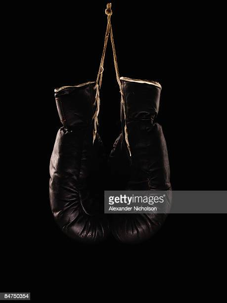 old black boxing gloves on black background - boxing gloves stock photos and pictures