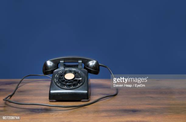 Old Black Rotary Telephone On Table Against Blue Background