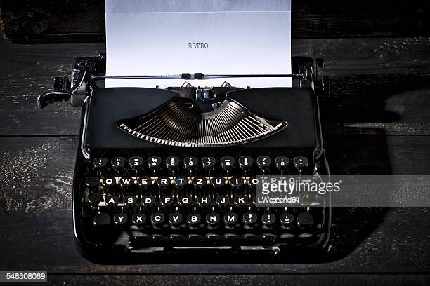 Old black typewriter on dark wood