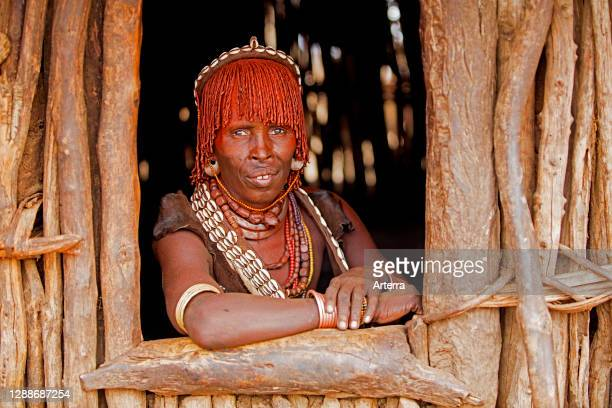 Old black woman of the Hamar / Hamer tribe looking through window in village in the Omo River valley, Debub Omo Zone, Southern Ethiopia, Africa.