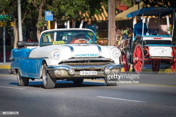 Old blue and white Pontiac vintage car driving in the 1st (first) Avenue, Varadero, Cuba