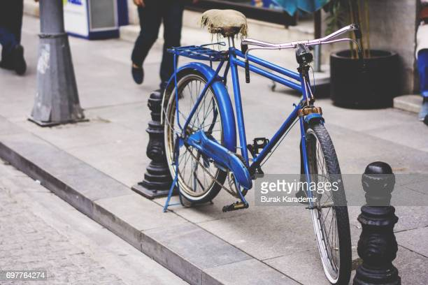 Old blue bicycle parkt on the street