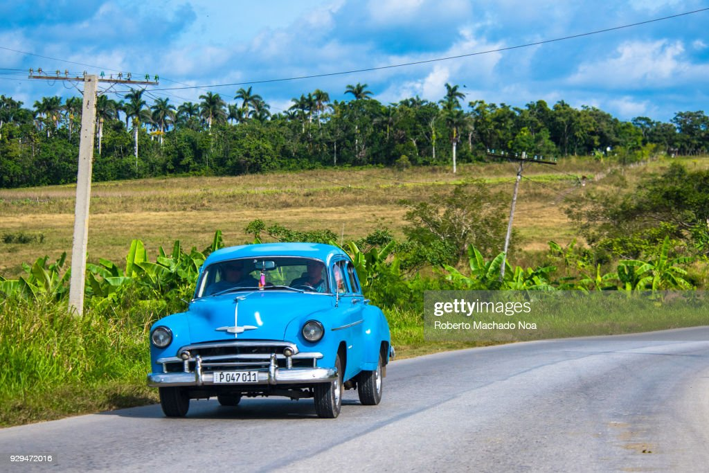 Old blue Chevrolet 50s car on a Cuban road during the