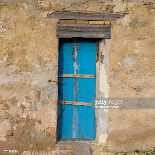 old blue door in a grungy concrete wall. old barn in sicily - finn bjurvoll stock photos and pictures
