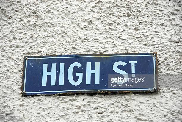 old blue metal 'high street' sign on a wall - lyn holly coorg stock pictures, royalty-free photos & images