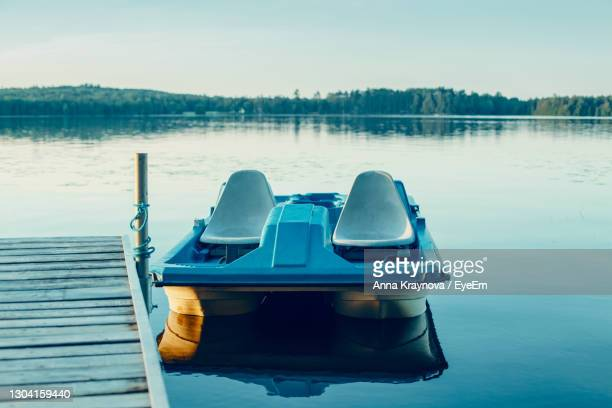 old blue pedal boat tied to wooden dock pier at canadian ontario lake in muskoka. travel canadian - ontario canada stock pictures, royalty-free photos & images