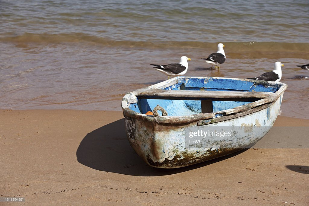 Old blue rowing boat on the beach : Stock Photo