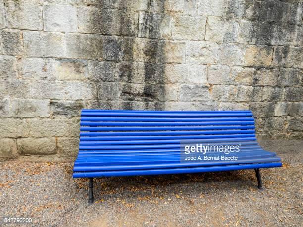 old blue wooden bench in a public park with an old stone wall - banco asiento fotografías e imágenes de stock