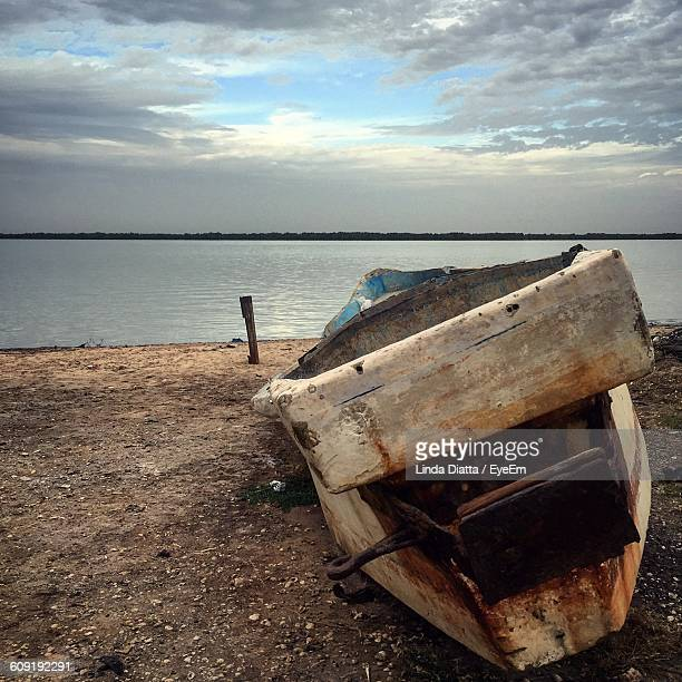 Old Boat Moored On Shore Against Cloudy Sky