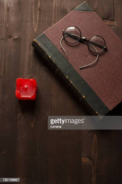 Old book, a red candle and spectacles on a wooden table