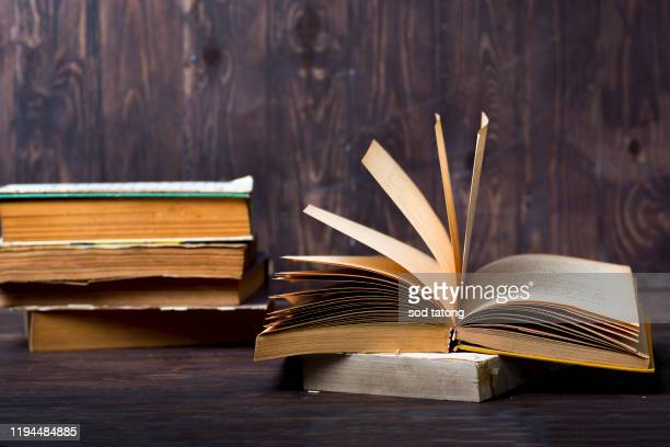 old book open on a wooden table with glasses - textbook stock pictures, royalty-free photos & images