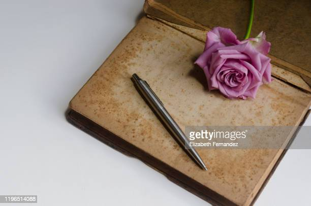 old book with pink rose and silver pen - ロマン主義 ストックフォトと画像
