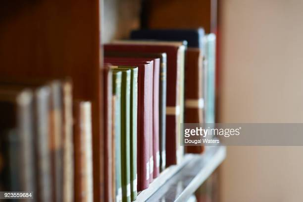 Old books lined up on a library shelf.