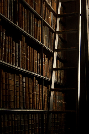 Old books on shelves in dark library and ladder - gettyimageskorea