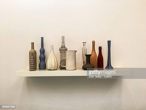 Old Bottles Arranged On Shelf At Wall