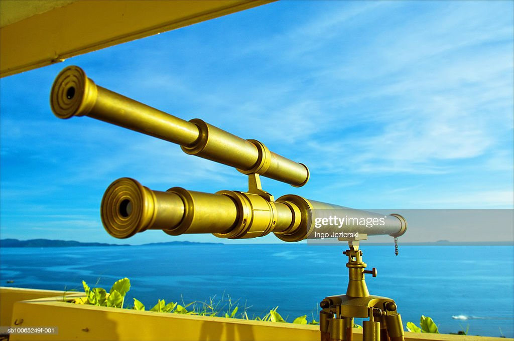 Old brass telescope on balcony aimed at small remote island : Foto stock