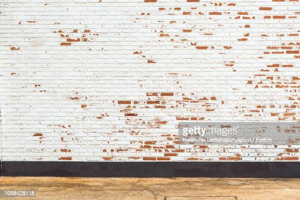 old brick wall by footpath - brick wall stock pictures, royalty-free photos & images
