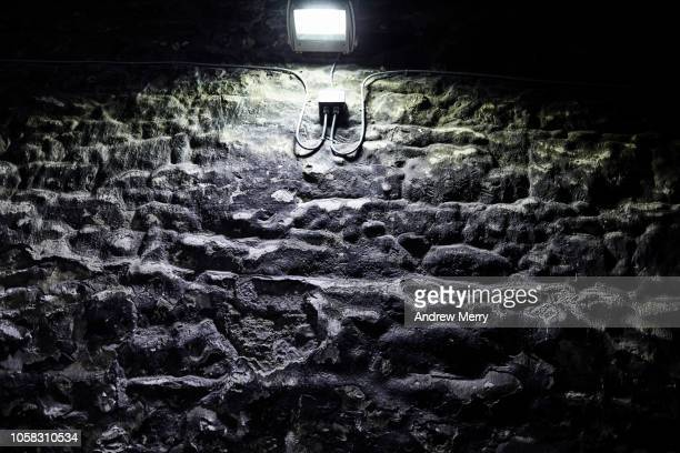 old brick wall, stone wall near edinburgh castle at night with bright street light illuminating the texture of the wall - sandstone wall stock pictures, royalty-free photos & images