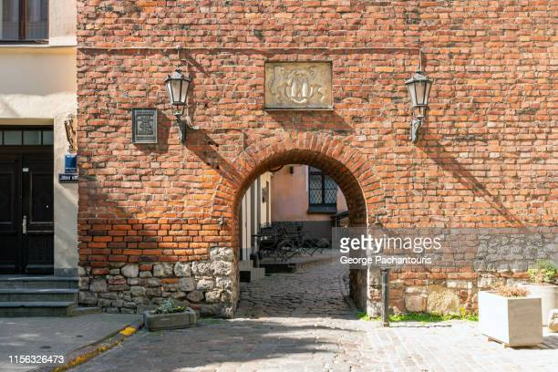 old brick wall with gate in riga, latvia - brick house stock pictures, royalty-free photos & images