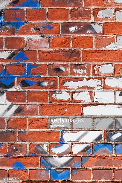 Old brick wall with remains of graffiti