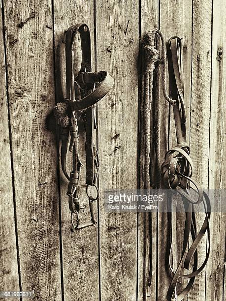 Old Bridles And Rope Hanging On Wooden Wall