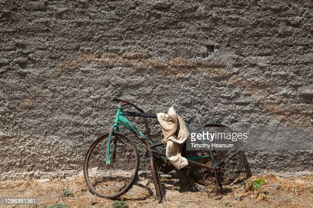 old, broken bicycle leaning against a rough-textured gray wall - timothy hearsum stock pictures, royalty-free photos & images