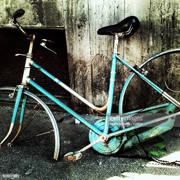 Old Broken Bicycle Leaning On Wooden Wall