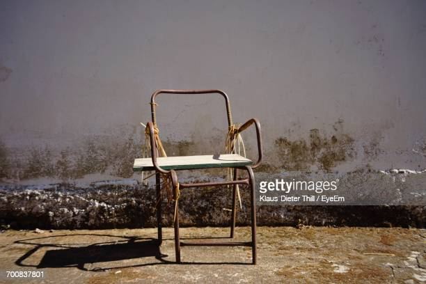 Old Broken Chair On Field Against Wall