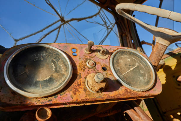 Old, broken vehicle dashboard and steering wheel inside abandoned truck