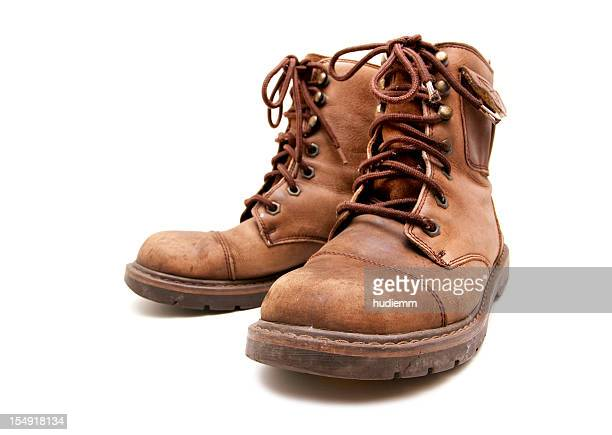 old brown boots isolated on white background - brown shoe stock photos and pictures