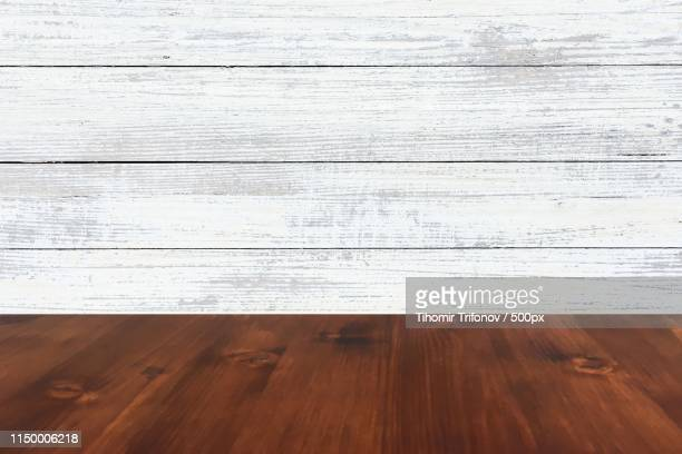 old brown oak wooden table on the blurry wood wall background, wood table - whitewashed stock pictures, royalty-free photos & images