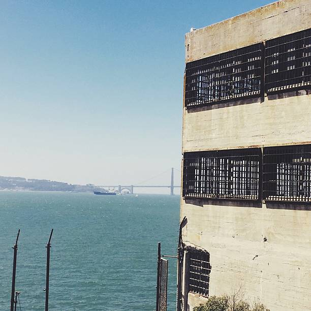 Old Building With View Of Golden Gate Bridge Over Bay Against Sky