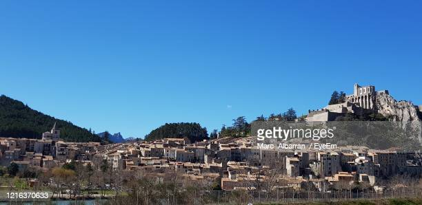 old buildings in town against clear blue sky - sisteron stock pictures, royalty-free photos & images