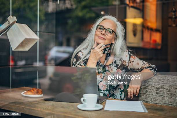 old business woman sitting in cafe alone - authors imagens e fotografias de stock
