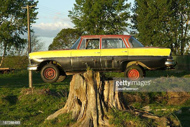 old car parked on tree stump - stranded stock photos and pictures