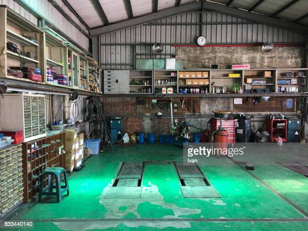 old car repair shop interior with mechanic in background - garage stock pictures, royalty-free photos & images