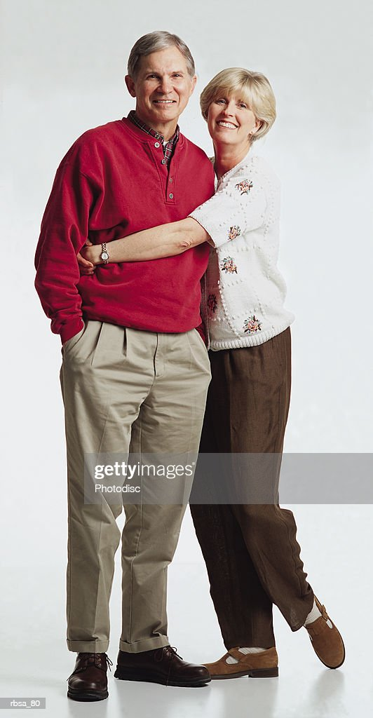 old caucasian adult male with gray hair wearing a red sweater and tan slacks stands while old caucasian adult female with blonde hair wearing a white sweater and brown slacks stands alongside him with her arms around his waist as the couple smiles at : Foto de stock