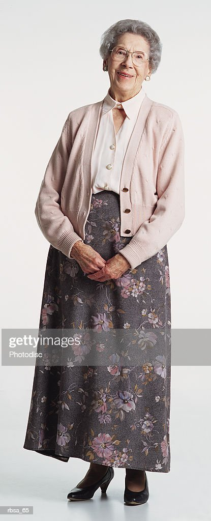 old caucasian female adult with short gray hair wears a pale pink sweater and floral skirt as she stands and smiles warmly at the camera : Foto de stock