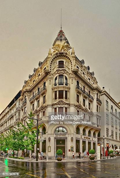 old central bank building (banco central) from 19th century on a rainy day, gran via street, granada centre, andalusia, spain - victor ovies fotografías e imágenes de stock