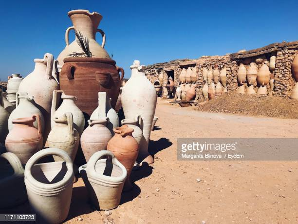 old ceramics containers on field against clear sky - djerba stock pictures, royalty-free photos & images