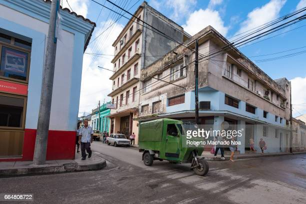 Old changed green tricycle or 'motoneta' used for transporting passenger inside the city Wide angle take of Cuban transportation and lifestyle