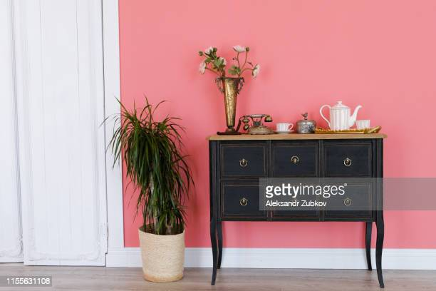 old chest of drawers with objects on the background of a pink wall. next flower in a pot, white door. beautiful interior in vintage style. - 家具 ストックフォトと画像