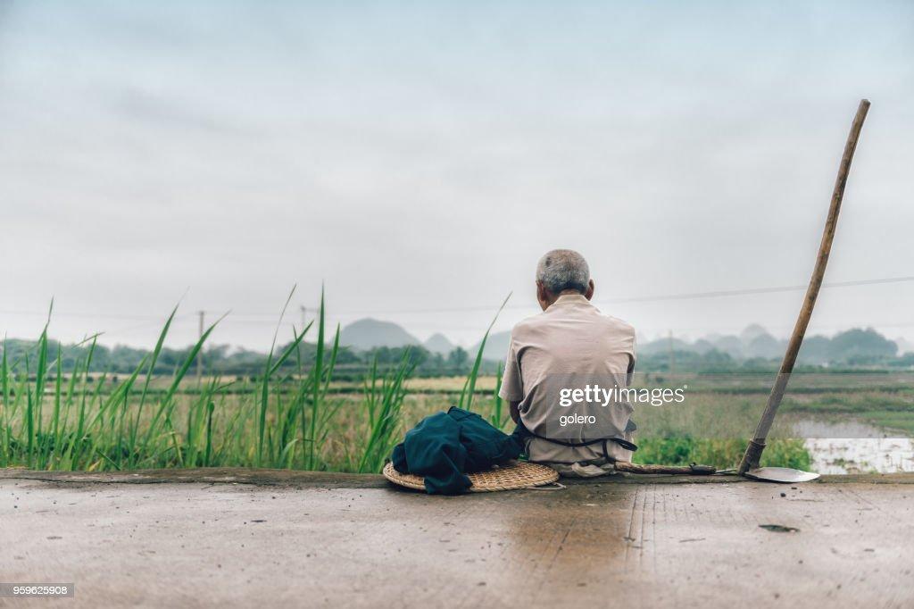 alte chinesische Bauer sitzt an Reisfeldern : Stock-Foto