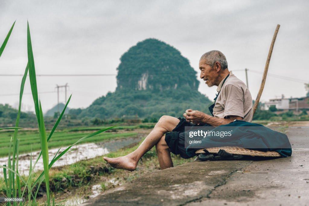 alte chinesische Bauer setzt sich für die Pause : Stock-Foto