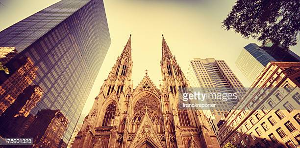 old church and tall skyscraper on manhattan - nyc - st. patricks cathedral manhattan stock photos and pictures