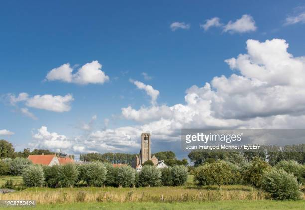 old church and trees on field against sky - damme stock pictures, royalty-free photos & images