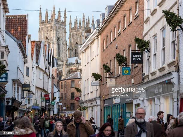 old city street view of york minster with the minster framed in the background as people pass along the street. - york stock photos and pictures